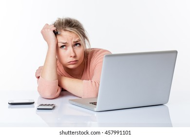 disillusioned beautiful blond girl blowing out her cheeks, lying on her white sparse desk, studying hard on her laptop thinking about her career, isolated white background