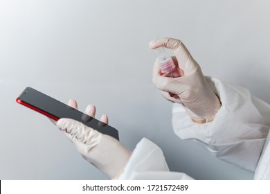 Disinfect your phone. Spraying alcohol to clean smartphone or cell phone during coronavirus covid-19 pandemic. Hand of nurse scientist wearing white protective bio hazard suit and sterile gloves