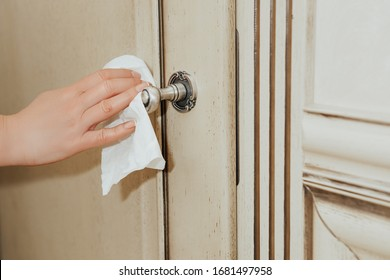 Disinfecting. Coronavirus COVID-19 Prevention cleaning woman wiping doorknob with antibacterial disinfecting wipe for killing corona virus. Protection and prophylaxis against the spread of the virus