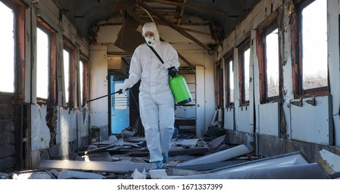Disinfection against virus. Doctor virologist in protective suit sprays medicine, disinfect walls. Quarantine, epidemic. Global biohazard.