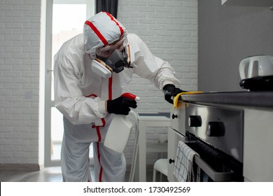 disinfection of coronavirus in the apartment. People in protective suits make professional cleaning of the room from viruses and diseases, infection removal service
