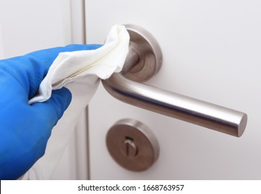 Disinfection in public places, the fight against the virus, coronavirus.Worker's hand wipes the door handles. A maid or housewife takes care of the house. Spring general or regular cleaning.