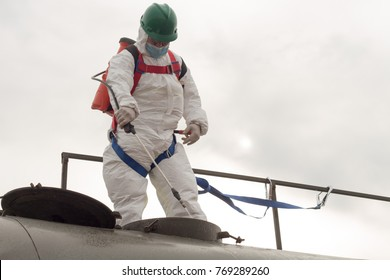 Disinfection specialist with disposable coveral is climbed to the top and cleaning and disinfecting water storage tank. Disinfection specialist during working at heights using PFAS, fall protection.