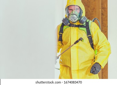 Disinfection For Virus Killing. Worker in Hazmat Suit and Face Protection Mask Spraying  Interior Using Chemical Agents To Stop Spreading Virus Infections.