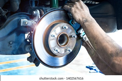 Disk brake and car disk brake system service concept - Car disk brake pad replacement service by hand of mechanic man in car garage with flare light effect and copy space