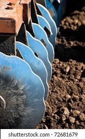 Disk harrow sitting in plowed soil