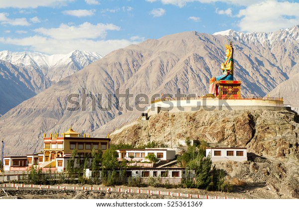 Diskit, India - June 22, 2012: Giant Buddha Maitreya sitting statue in Nubra valley against the backdrop of the Himalayan mountains in Diskit monastery, Himalayas, northern India