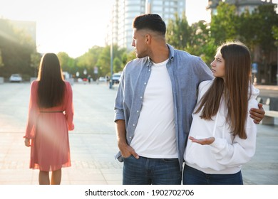 Disloyal man looking at another woman while walking with his girlfriend outdoors