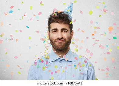 Dismal gloomy male student celebrates his succesful passed exam, looks tired after sleepless night of preparation, meets with groupmates. Young attractive businessman commemorates triumph at work