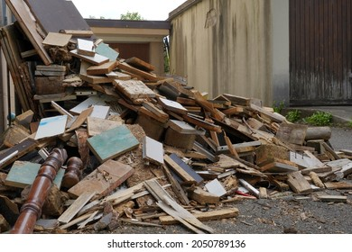 Dismantled furniture on a yard between two buildings. There are pieces of wooden furniture piled up. They are of irregular size. It looks like vacating of a dwelling.