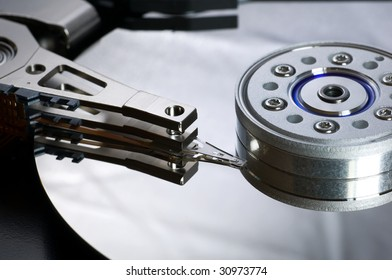 Dismantled hard drive showing platter and read/write head