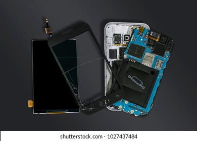 Dismantled mobile phone with broken display screen isolated on dark grey background