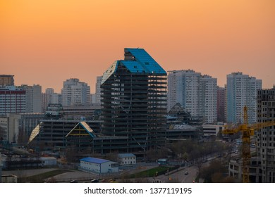Dismantlement of blue glass skyscraper at sunset cityscape, broken down large abandoned building during demolition, Moscow