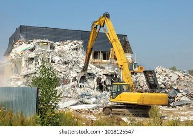 Dismantling of concrete structures, excavators break down old buildings