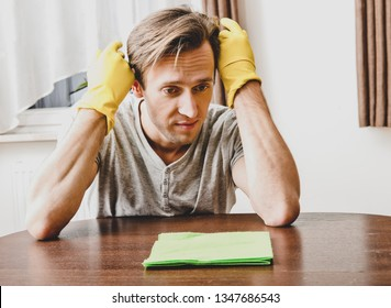 Dismay man with rubber gloves cleaning house. Housekeeper concept.