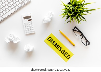 Dismissal concept. Sign Dismissed on office desk with computer keyboard and crumpled paper on white background top view