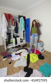 Disorder and mess at home. Cheerful young girl.