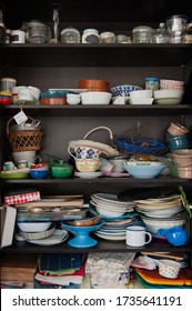 Disorganised kitchen cupboard with stacks of mismatched ceramic plates and bowls, piles of mugs and glasses and lots of jars and vases randomly shoved onto the shelves
