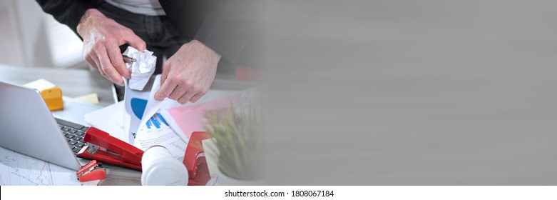 Disorganized businessman looking for documents on his messy desk; panoramic banner