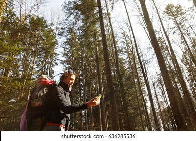 Disoriented hiker checking her phone for GPS coordinates, being lost in the woods, looking for the right direction. Adventure, active lifestyle, mobile phone dependency, being lost concept.