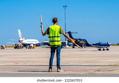 Dispatcher geaturing signs directing the blue shiny sport plane on the airport runway