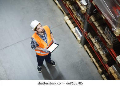 Dispatcher in helmet and uniform making inventory in storehouse