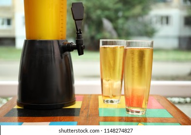 Dispenser and glasses with cold beer on table