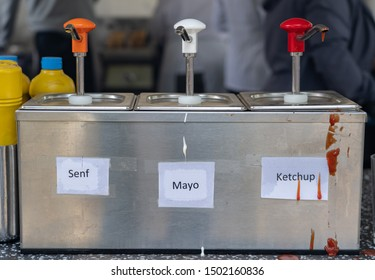 Dispenser for mustard, mayonnaise and ketchup at a wurst stall, with the German words for mustard, mayonnaise and ketchup
