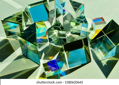 Dispersion of light, group mixture of dichroic glass cube, triangular prism, convex concave lens angled randomly splitting a beam of sunlight into spectrum colours refection refraction of light