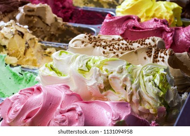 Display of assorted ice creams in metal tubs in a shop or ice cream parlour