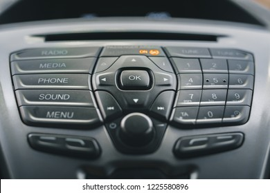 Display of audio system panel with media, phone, sound, radio and menu buttons. Modern car control panel with radio control and dial pad.  Control panel of a transport van.