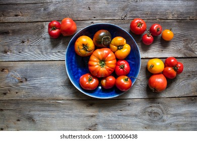 display of big and small tomatoes for organic gardening, healthy agriculture or vegan food with cracks and imperfections over vintage wooden table, flat lay in studio