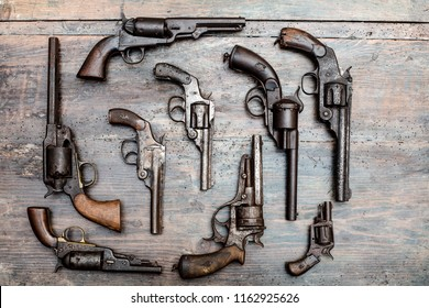 Display case with old historical guns and pistols on a vintage wood background in an exhibit in a museum or collectors showcase
