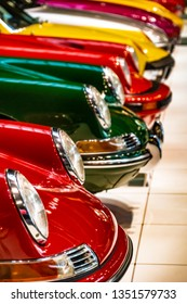 Display of colorful classic sports cars parked next to each other in an exhibit hall
