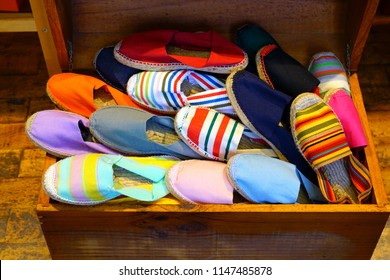 Display of colorful traditional espadrilles cord and fabric shoes in a trunk in the Basque country, France