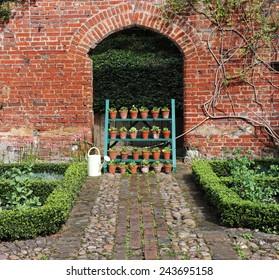Display of Flowerpots under a red brick archway
