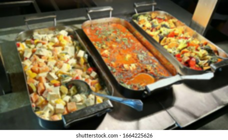 Display of food at an evening buffet at a tourist hotel. Blurred view