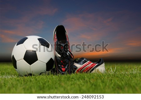9a121f430 Display of football ball and soccer shoe on the grass at dust time