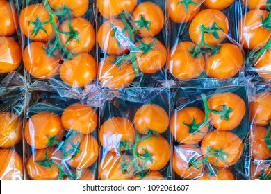 Display of fresh plastic wrapped orange cherry tomatoes