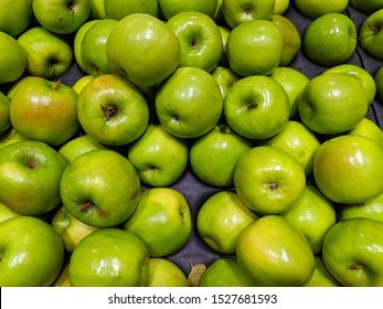 Display of green Granny-Smith apples, slightly damaged seconds for local consumption in Australia. Non export quality apples, most with minor damage from machine sorting, sold locally.