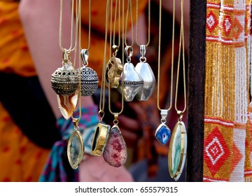 Display of handcrafted  artisan necklaces with semi-precious stones, silver pewter and gold jewellery  for sale on an international market stall