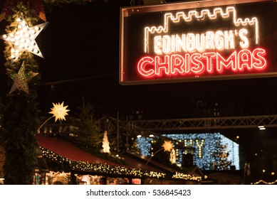 A display of lights and a Neon sign at the entrance of the Edinburgh Christmas Market and Fair in Princes Street Gardens, Edinburgh, UK, welcomes people from around the world during the festive season