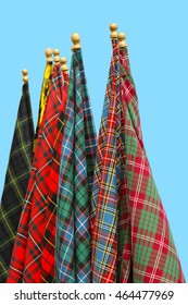 display of many Tartan flags hanging on flag poles in front of a blue background