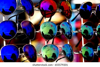 Display of multicolored mirrored sunglasses showing reflections of festival scenes and people walking around at a vendor's market stall