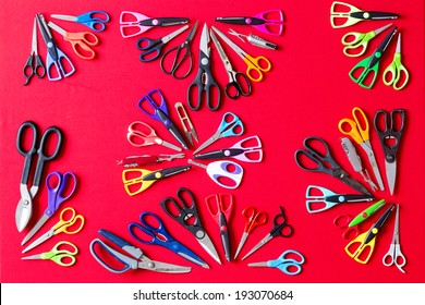 Display of multiple different pairs of domestic scissors on red conceptual of scissors for everyone and for every different task, overhead view