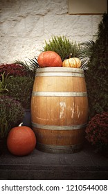 A display of pumpkins ona  wooden barrel outside a building in muted tones