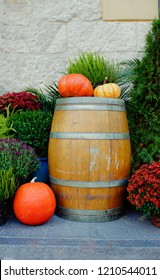 A display of pumpkins ona  wooden barrel outside a building in cool tones