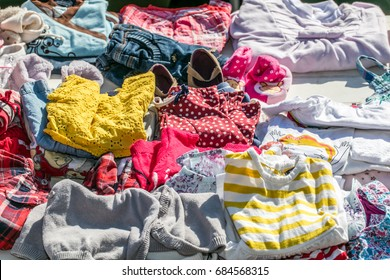 display of second hand baby and children clothes for reusing, reselling,recycling,donating or welfare for second life sold at outdoor garage sale