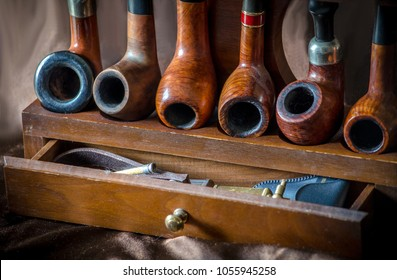 display of smoking pipes on a wood rack, with an accesory drawer of pipe tools