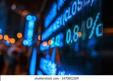 Display of Stock market quotes with city lights reflect on glass